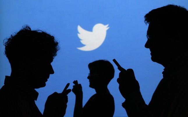 People holding mobile phones are silhouetted against a backdrop projected with the Twitter logo in this illustration picture taken in Warsaw in this September 27, 2013 file photo. Twitter Inc on April 29, 2014, reported 255 million monthly active users, up 5.8 percent from the previous quarter but not enough to satisfy investors increasingly concerned about its struggle to gain a mass following. REUTERS/Kacper Pempel/Files (POLAND - Tags: BUSINESS TELECOMS LOGO)